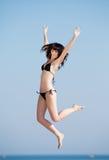 Молодая женщина скача на открытый воздух Стоковые Изображения