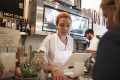 Молодая женщина служа клиент в магазине мясника стоковые изображения rf