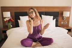 Молодая женщина слушает музыка используя наушники и smartphone стоковое фото rf