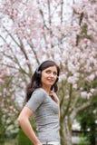 Молодая женщина слушая музыку на беспроводных наушниках в парке с деревьями вишневого цвета стоковое фото rf