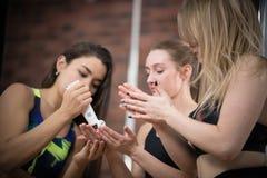 Молодая женщина смазывает руки танцоров со сливками студия стоковые фотографии rf