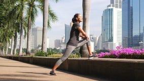 Молодая женщина смешанной гонки атлетическая делая нагревающ протягивать перед бежать в парке утра замедленное движение 4k Бангко акции видеоматериалы