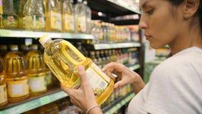Молодая женщина смешанной гонки выбирая оливковое масло в супермаркете Ингредиенты чтения клиента обозначают в магазине 4K сток-видео