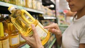 Молодая женщина смешанной гонки выбирая оливковое масло в супермаркете Ингредиенты чтения клиента обозначают в магазине 4K акции видеоматериалы