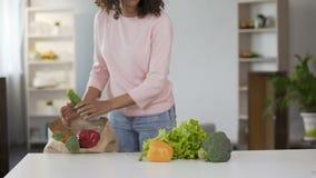 Молодая женщина смешанной гонки кладя овощи на таблицу после посещения магазина бакалеи сток-видео