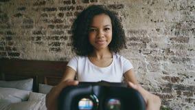 Молодая женщина смешанной гонки кладя стекла шлемофона человеческого лица VR 360 виртуальной реальности сток-видео