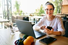 Молодая женщина смешанной гонки работая с компьтер-книжкой в кафе смотря камеру Азиатский кавказский женский изучать используя ин Стоковое фото RF