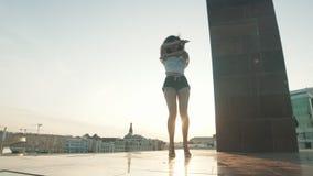 Молодая женщина смешанной гонки с вьющиеся волосы выполняя привлекательные танцы на предпосылке современных зданий - заходе солнц сток-видео