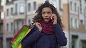Молодая женщина смешанной гонки с хозяйственными сумками вызывая такси, удовлетворенное с приобретениями видеоматериал
