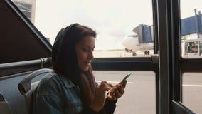 Молодая женщина смешанной гонки туристская в шине используя передвижной умный телефон на авиапорте 4K сток-видео