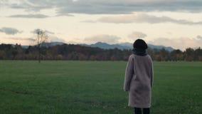 Молодая женщина смотрит горы в осени акции видеоматериалы