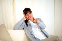 Молодая женщина смотря вас с remote tv Стоковые Фото