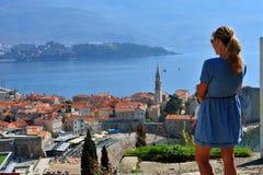 Молодая женщина смотря городок Budva старый стоковое изображение rf