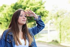 Молодая женщина смотря далеко с рукой на ее лбе стоковое фото rf