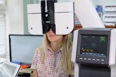 Молодая женщина смотря машину испытания глаза рефрактометра в офтальмологии стоковые фото