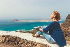Молодая женщина смотря на море стоковое фото