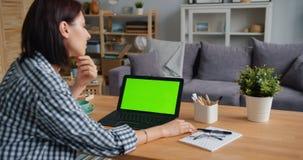 Молодая женщина смотря средства массовой информации зеленого экрана ноутбука модель-макета наблюдая дома акции видеоматериалы