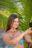 Молодая женщина со смартфоном перед ладонью стоковая фотография rf