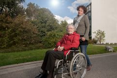 Молодая женщина со старшей женщиной сидя в кресло-коляске стоковые изображения rf