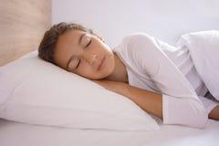 Молодая женщина спать в кровати стоковые фото