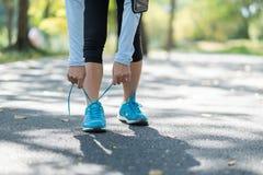 Молодая женщина спортсмена связывая ботинки бега в парке на открытом воздухе, женский бегуна готовый для jogging на дороге снаруж стоковые фото