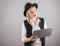 Молодая женщина стиля битника в шляпе используя планшет Серая monochrome предпосылка Стоковая Фотография RF