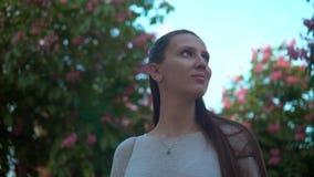 Молодая женщина стоит в парке зацветая розовых каштанов Красивая женщина и зацветая розовые деревья в парке сток-видео