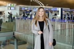 Молодая женщина стоя на авиапорте, нося пальто Стоковое фото RF