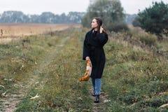 Молодая женщина стоя на дороге в coutryside Осень, пасмурная погода Стоковые Изображения RF