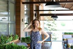 Молодая женщина стоя на кафе около зеленых растений с поднятой рукой Стоковые Изображения RF