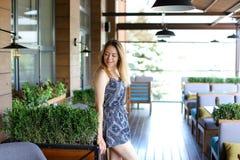 Молодая женщина стоя на кафе около зеленых palnts Стоковое Изображение RF