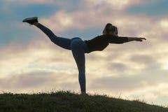 Молодая женщина стоя на одной ноге и работая на разминке утра травы, красивом восходе солнца стоковые фотографии rf