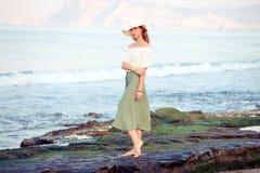 Молодая женщина стоя на утесе стоковое изображение