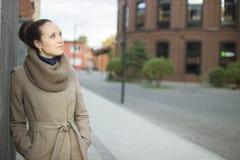 Молодая женщина стоя около стены Стоковые Изображения RF