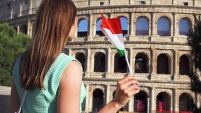Молодая женщина стоя около Colosseum в Риме, Италии Девочка-подросток развевая итальянский флаг в замедленном движении видеоматериал