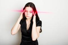 Молодая женщина страдает от головной боли Портрет девушки схватывая ее голову Мигрени и проблемы кровяного давления стоковое фото rf