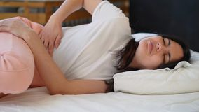 Молодая женщина страдая от боли в животе пока сидящ на кровати дома акции видеоматериалы