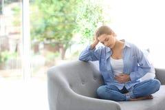 Молодая женщина страдая от менструальных корч стоковые фотографии rf