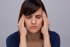 Молодая женщина страдая от сильной головной боли, держащ пальцы к ее вискам и глаза заключения от боли, prepairing для того чтобы стоковое изображение