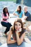 Молодая женщина сь с друзьями Стоковое Фото