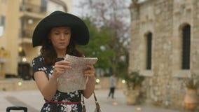 Молодая женщина с багажом и карта в выпаданных из ускорения руках, находках правильное направление сток-видео