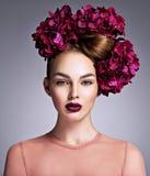 Молодая женщина с букетом пурпурных цветков в ее волосах стоковая фотография