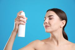 Молодая женщина с бутылкой термальной воды на предпосылке цвета стоковое фото