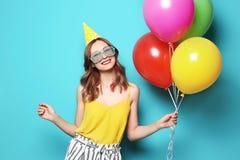 Молодая женщина с воздушными шарами на предпосылке цвета Торжество дня рождения стоковое изображение rf