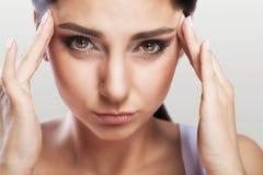 Молодая женщина с головной болью, которая держит ее голову, на серой предпосылке, macrophotography, мигрень, красивая девушка, пр Стоковая Фотография RF