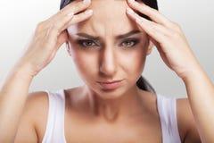 Молодая женщина с головной болью, которая держит ее голову, на серой предпосылке, macrophotography, мигрень, красивая девушка, пр Стоковая Фотография