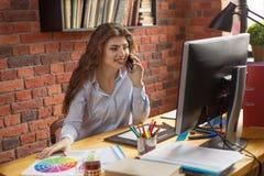 Молодая женщина с длинными волосами работая дома или в офисе стиля просторной квартиры Она говоря через смартфон и усмехаться Диз стоковые изображения rf