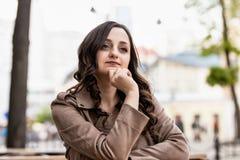 Молодая женщина с длинными каштановыми волосами на таблице на фоне улицы, dreamily смотря в расстояние стоковая фотография rf