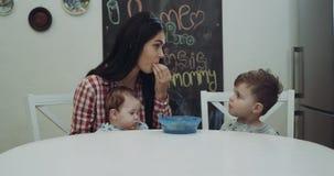 Молодая женщина с ее ребенком s сидит на кухонном столе, играя и тратящ время совместно, дается один из детей акции видеоматериалы
