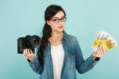 Молодая женщина с камерой и наличными деньгами Стоковое фото RF